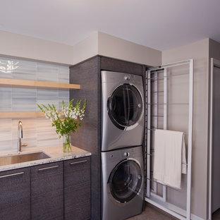 Idée de décoration pour une buanderie minimaliste de taille moyenne avec un évier encastré, un placard à porte plane, des portes de placard grises, un plan de travail en granite, sol en stratifié, des machines superposées, un sol multicolore et un mur gris.