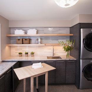 Idéer för ett mellanstort modernt l-format grovkök, med en undermonterad diskho, släta luckor, grå skåp, granitbänkskiva, beige väggar, laminatgolv, en tvättpelare och flerfärgat golv