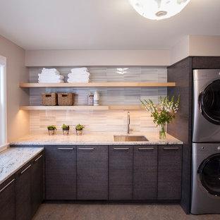 Idéer för mellanstora funkis l-formade tvättstugor, med en undermonterad diskho, släta luckor, grå skåp, granitbänkskiva, beige väggar, laminatgolv, en tvättpelare och flerfärgat golv