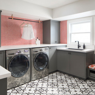 Photo of a large contemporary u-shaped utility room in San Francisco with an undermount sink, flat-panel cabinets, grey cabinets, ceramic floors, a side-by-side washer and dryer, white benchtop and wallpaper.