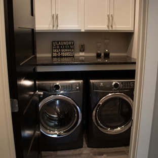 Inspiration for a small industrial laundry cupboard in Other with shaker cabinets, beige cabinets, quartz benchtops, beige walls, light hardwood floors, a side-by-side washer and dryer, grey floor and black benchtop.