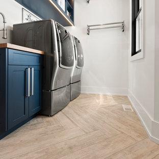 Klassisk inredning av en mellanstor blå linjär blått tvättstuga enbart för tvätt, med en undermonterad diskho, skåp i shakerstil, blå skåp, träbänkskiva, vita väggar, ljust trägolv, en tvättmaskin och torktumlare bredvid varandra och beiget golv
