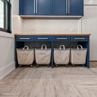 Cette image montre une buanderie linéaire design dédiée et de taille moyenne avec un évier encastré, un placard à porte shaker, des portes de placard bleues, un plan de travail en bois, un mur blanc, un sol en bois clair, des machines côte à côte, un sol beige et un plan de travail bleu.