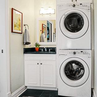 Foto di una lavanderia multiuso tradizionale di medie dimensioni con lavello sottopiano, ante con riquadro incassato, ante bianche, top in granito, pareti beige, pavimento in gres porcellanato e lavatrice e asciugatrice a colonna