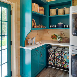 Inspiration for a mid-sized country l-shaped dedicated laundry room in Boston with ceramic floors, shaker cabinets, blue cabinets, a side-by-side washer and dryer, beige floor, white benchtop and wood walls.