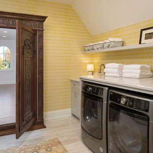 Inspiration for a large traditional single-wall separated utility room in Minneapolis with recessed-panel cabinets, grey cabinets, yellow walls, a side by side washer and dryer, beige floors, marble worktops and light hardwood flooring.