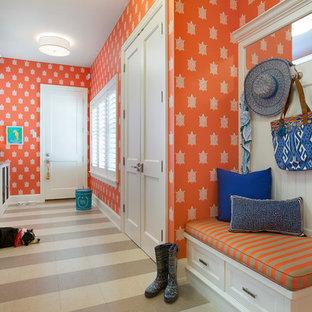 ミネアポリスのトラディショナルスタイルのおしゃれな家事室 (ll型、落し込みパネル扉のキャビネット、白いキャビネット、オレンジの壁、左右配置の洗濯機・乾燥機) の写真