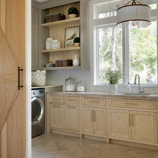 Immagine di una sala lavanderia country con lavello sottopiano, ante con riquadro incassato, ante in legno chiaro, pareti bianche, lavatrice e asciugatrice affiancate, pavimento beige e top beige