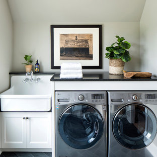 Inspiration for a traditional separated utility room in Minneapolis with recessed-panel cabinets, white cabinets, a side by side washer and dryer, a belfast sink, grey floors, black worktops and grey walls.
