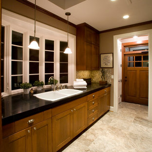 Inspiration for a large traditional galley separated utility room in Portland with a double-bowl sink, shaker cabinets, medium wood cabinets, granite worktops, beige walls, travertine flooring, a stacked washer and dryer, beige floors and black worktops.