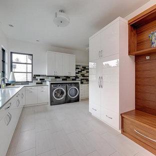 Modern inredning av ett mycket stort grå l-format grått grovkök, med en undermonterad diskho, släta luckor, vita skåp, bänkskiva i kvarts, laminatgolv, en tvättmaskin och torktumlare bredvid varandra, grått golv och vita väggar