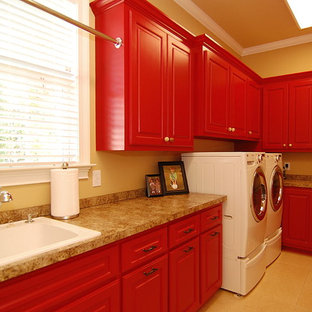 Photo of a large classic u-shaped utility room in Charleston with a built-in sink, raised-panel cabinets, red cabinets, laminate countertops, brown walls, ceramic flooring, a side by side washer and dryer and beige floors.