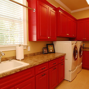 Large traditional u-shaped utility room in Charleston with a built-in sink, raised-panel cabinets, red cabinets, laminate countertops, brown walls, ceramic flooring, a side by side washer and dryer and beige floors.