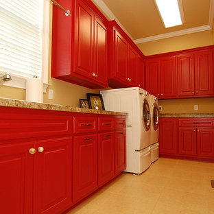 Large classic u-shaped utility room in Charleston with a built-in sink, raised-panel cabinets, red cabinets, laminate countertops, brown walls, ceramic flooring, a side by side washer and dryer and beige floors.