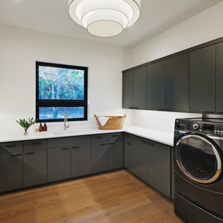 Example of a large trendy u-shaped medium tone wood floor and brown floor utility room design in Austin with an undermount sink, flat-panel cabinets, gray cabinets, quartzite countertops, white walls, a side-by-side washer/dryer and white countertops