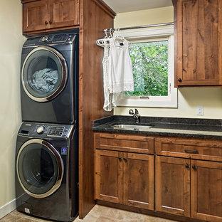 Immagine di una sala lavanderia american style di medie dimensioni con lavello sottopiano, ante in stile shaker, ante in legno scuro, top in granito, pareti beige, pavimento in gres porcellanato, lavatrice e asciugatrice a colonna, pavimento beige e top nero