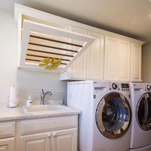Idéer för ett mellanstort lantligt l-format grovkök, med en allbänk, luckor med upphöjd panel, vita skåp, laminatbänkskiva, beige väggar, klinkergolv i porslin, en tvättmaskin och torktumlare bredvid varandra och beiget golv