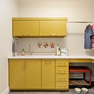 Inredning av en modern mellanstor vita l-formad vitt tvättstuga enbart för tvätt, med en undermonterad diskho, släta luckor, gula skåp, vita väggar, en tvättpelare, grått golv, bänkskiva i kvarts och klinkergolv i porslin