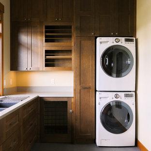 Ispirazione per una sala lavanderia stile rurale di medie dimensioni con lavello a doppia vasca, ante in stile shaker, pareti bianche, lavatrice e asciugatrice a colonna e ante in legno bruno