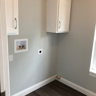 Design ideas for an utility room in Other with recessed-panel cabinets, white cabinets, engineered stone countertops, grey walls, vinyl flooring, a side by side washer and dryer, brown floors and black worktops.