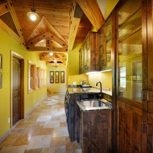 Aménagement d'une buanderie linéaire sud-ouest américain avec un évier encastré, un placard à porte shaker, des portes de placard en bois sombre, un mur vert, un sol beige, un plan de travail gris, un plafond voûté et un plafond en bois.