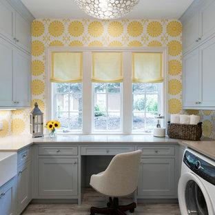 Idee per una sala lavanderia stile marino con lavello stile country, ante grigie, pareti gialle, parquet chiaro, lavatrice e asciugatrice affiancate, pavimento beige e ante in stile shaker