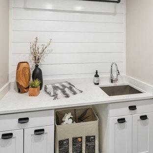 Immagine di una piccola sala lavanderia country con lavello sottopiano, ante in stile shaker, ante bianche, top in quarzo composito, pareti grigie, pavimento con piastrelle in ceramica, lavatrice e asciugatrice affiancate, pavimento nero e top bianco