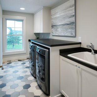 This is an example of a medium sized traditional galley separated utility room in Minneapolis with a built-in sink, shaker cabinets, white cabinets, laminate countertops, white walls, porcelain flooring, a side by side washer and dryer, multi-coloured floors and black worktops.