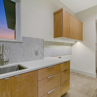 Inspiration for a large modern u-shaped porcelain tile and multicolored floor utility room remodel in Austin with an undermount sink, flat-panel cabinets, medium tone wood cabinets, quartz countertops, white walls, a side-by-side washer/dryer and turquoise countertops