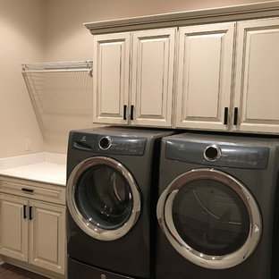 Photo of a large classic single-wall separated utility room in Milwaukee with raised-panel cabinets, white cabinets, composite countertops, grey walls, dark hardwood flooring, a side by side washer and dryer, brown floors and white worktops.