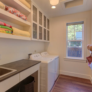 Photo of a small farmhouse galley separated utility room in Austin with a built-in sink, shaker cabinets, white cabinets, laminate countertops, white walls, vinyl flooring, a side by side washer and dryer, brown floors and black worktops.
