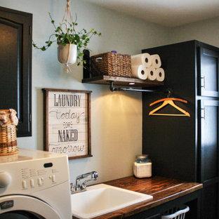 Industriell inredning av en mellanstor bruna linjär brunt tvättstuga enbart för tvätt, med en allbänk, skåp i shakerstil, svarta skåp, träbänkskiva, blå väggar, linoleumgolv, en tvättmaskin och torktumlare bredvid varandra och beiget golv