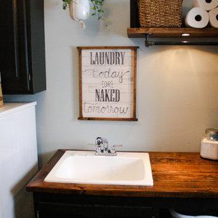 Diseño de cuarto de lavado lineal, urbano, de tamaño medio, con pila para lavar, armarios estilo shaker, puertas de armario negras, encimera de madera, paredes azules, suelo de linóleo, lavadora y secadora juntas, suelo beige y encimeras marrones