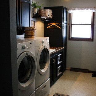 Idéer för att renovera en mellanstor industriell bruna linjär brunt tvättstuga enbart för tvätt, med en allbänk, skåp i shakerstil, svarta skåp, träbänkskiva, blå väggar, linoleumgolv, en tvättmaskin och torktumlare bredvid varandra och beiget golv