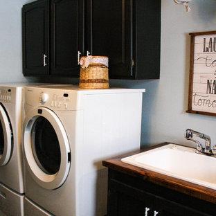 Foto di una sala lavanderia industriale di medie dimensioni con lavatoio, ante in stile shaker, ante nere, top in legno, pareti blu, pavimento in linoleum, lavatrice e asciugatrice affiancate, pavimento beige e top marrone