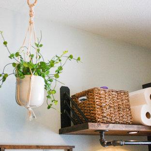 Inredning av en industriell mellanstor bruna linjär brunt tvättstuga enbart för tvätt, med en allbänk, skåp i shakerstil, svarta skåp, träbänkskiva, blå väggar, linoleumgolv, en tvättmaskin och torktumlare bredvid varandra och beiget golv