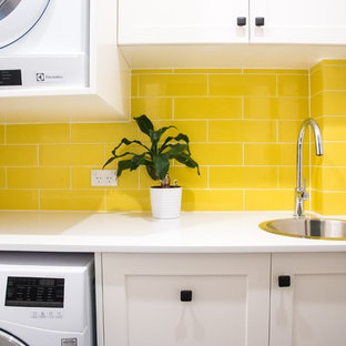 Design ideas for a small contemporary l-shaped dedicated laundry room in Sydney with a drop-in sink, shaker cabinets, white cabinets, quartz benchtops, white walls, porcelain floors and a stacked washer and dryer.