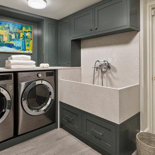 Inredning av en klassisk beige beige tvättstuga, med en allbänk, skåp i shakerstil, grå skåp, en tvättmaskin och torktumlare bredvid varandra och grått golv