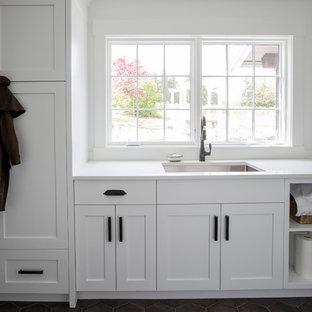 Idee per una sala lavanderia country con ante in stile shaker, ante bianche, top in marmo, pareti bianche, pavimento in terracotta, lavatrice e asciugatrice a colonna, pavimento nero e lavello sottopiano