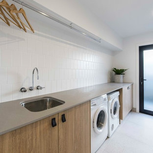 Photo of a contemporary single-wall dedicated laundry room in Brisbane with an undermount sink, medium wood cabinets, white walls, ceramic floors, a side-by-side washer and dryer, flat-panel cabinets, grey floor and beige benchtop.