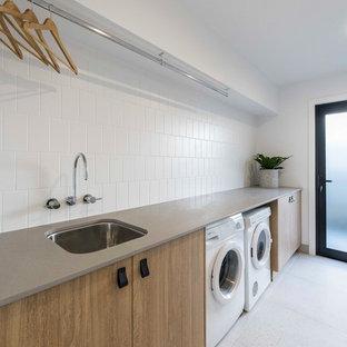 Esempio di una sala lavanderia contemporanea con lavello sottopiano, ante in legno scuro, pareti bianche, pavimento con piastrelle in ceramica, lavatrice e asciugatrice affiancate, ante lisce, pavimento grigio e top beige