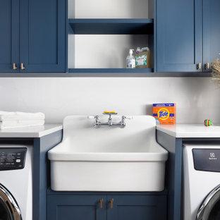 Idéer för mellanstora lantliga vitt tvättstugor enbart för tvätt, med en allbänk, skåp i shakerstil, blå skåp, bänkskiva i kvarts, vita väggar och en tvättmaskin och torktumlare bredvid varandra