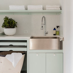 Mid-sized trendy ceramic floor and gray floor dedicated laundry room photo in New York with a farmhouse sink, flat-panel cabinets, green cabinets, quartzite countertops and white walls