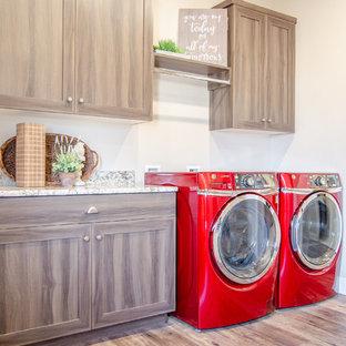 Ispirazione per una grande lavanderia multiuso country con lavello a doppia vasca, ante con riquadro incassato, top in granito e lavatrice e asciugatrice affiancate