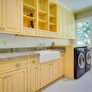 Bild på en stor lantlig grå linjär grått tvättstuga enbart för tvätt, med en rustik diskho, granitbänkskiva, gröna väggar, klinkergolv i keramik, en tvättmaskin och torktumlare bredvid varandra, gula skåp och luckor med profilerade fronter