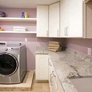 Foto på en stor vintage l-formad tvättstuga enbart för tvätt, med en undermonterad diskho, skåp i shakerstil, vita skåp, granitbänkskiva, lila väggar, klinkergolv i porslin och en tvättmaskin och torktumlare bredvid varandra