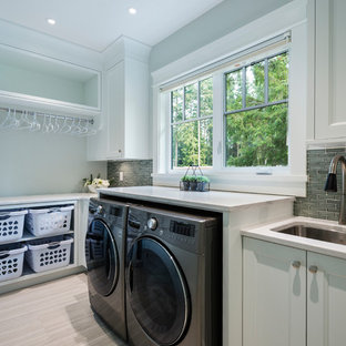 Inspiration for a large traditional single-wall utility room in Vancouver with a submerged sink, recessed-panel cabinets, white cabinets, engineered stone countertops, white walls, porcelain flooring, a side by side washer and dryer and grey floors.