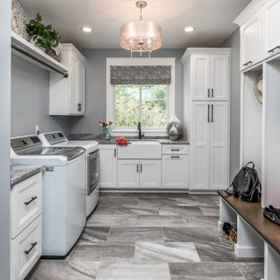 Example of a transitional l-shaped gray floor utility room design in Indianapolis with a farmhouse sink, recessed-panel cabinets, white cabinets, gray walls and gray countertops