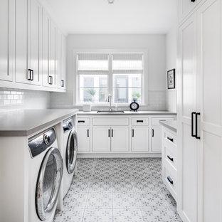Ispirazione per una sala lavanderia costiera con lavello sottopiano, ante in stile shaker, ante bianche, pareti bianche, lavatrice e asciugatrice affiancate, pavimento multicolore e top grigio
