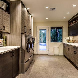 Exemple d'une buanderie parallèle rétro multi-usage et de taille moyenne avec un évier utilitaire, un placard à porte plane, des portes de placard grises, un plan de travail en quartz modifié, un mur blanc, un sol en carrelage de porcelaine, des machines côte à côte et un sol gris.